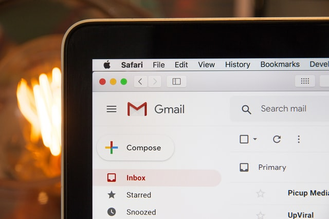 Corner of macbook, with partial screen visible. Gmail email account information and logo seen.